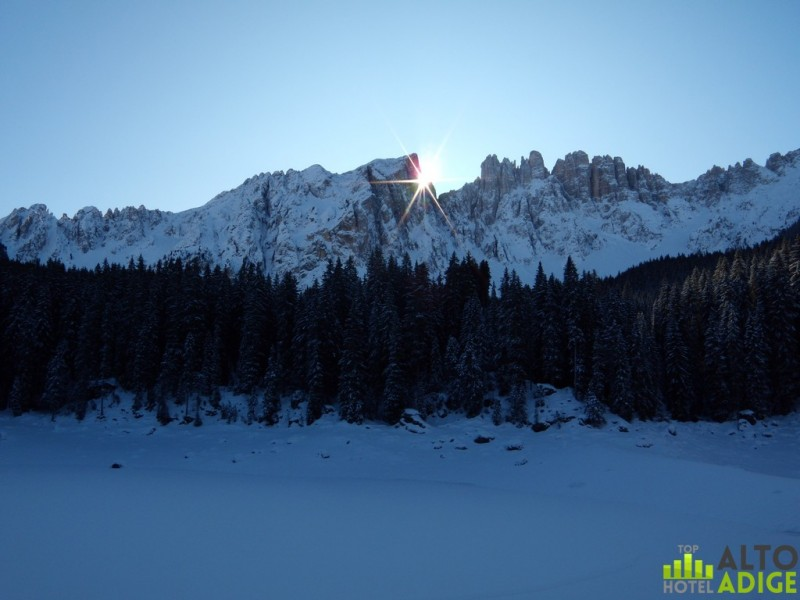 The sun behind the Latemar at Carezza's Lake