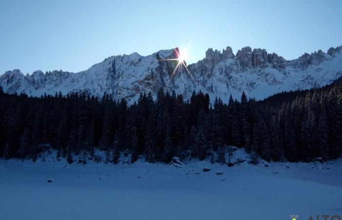 Galleria Fotografica Alto Adige Al lago di Carezza il sole fa capolino dietro al Latemar